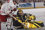 2/12/05  Omaha, NE University of Nebraska at Omaha's Alex Nikiforuk gets tied up with Michigan goalie Al Montoya. (photo by Chris Machian/ Prarie Pixel Group)
