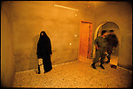 Palestinian police search a Hamas home in the middle of the night. They found only this woman and some warm, empty beds. Jabalyah refugee camp, Gaza, March, 1996.