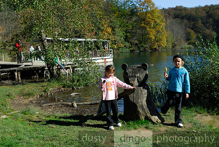 Two children (5 years old, 9 years old) eating ice-cream by a wooden sculpture of a bear. Plitvice National Park, Croatia