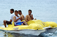 Jordan. Aqaba. Aqaba is a holiday resort and a harbour on the Red Sea. Jordanians men enjoy a rented yellow pedal boat ride in the Gulf of Aqaba, which is divided between three countries: Jordan, Israel and Egypt. Men wear bermuda shorts.  © 2002 Didier Ruef
