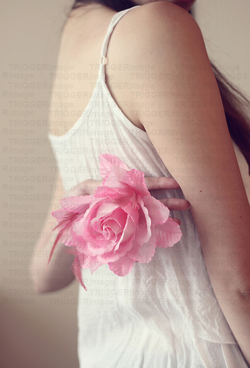 girl holding a pink rose behind her back