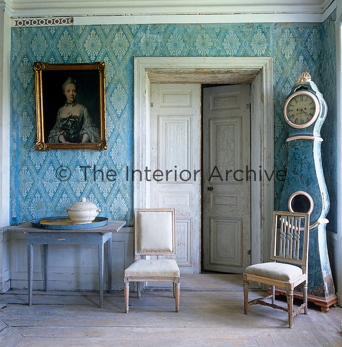 The blue of the case clock matches that of the French Directoire patterned wallpaper in the dining room