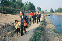 China. Province of Henan. Village Nan Laoguanzui. A grandmother holds the arm of her granddaughter. An old woman, having problems to walk alone, is helped and hold on both her arms by two men on the river bank.  © 2004 Didier Ruef