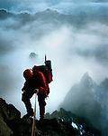 Steve Cooke abseils the Southwest Ridge Route of Mount Kenya as a storm clears.  The summit of Point John 4883m (16,020ft) is visible behind and below.  Point Slade 4750m (15,584ft) is the pinnacle on the right.