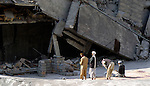 Following an October 8, 2005, earthquake, men pray outside the ruins of a mosque in the devastated town of Balakot. The quake measured 7.6 on the Richter scale and killed more than 74,000 people in northern Pakistan.