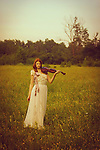 Female youth outdoors in spring wearing a white gown and holding a violin.