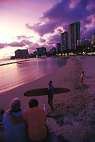 Elderly couple on vacation talking with mature surfer on beach at sunset at the seawall at Kuhio Beach, people wading in water in background Waikiki, Oahu