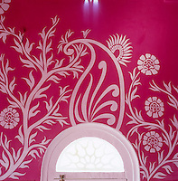 Detail of a white floral motif painted around the window on the bright pink walls of the living room
