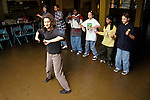 Berkeley CA Young woman volunteer teaching junior high school students folk dancing in after-school program