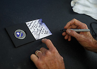 Mar 20, 2016; Gainesville, FL, USA; NHRA funny car driver Jack Beckman autographs an Infinite Hero Foundation challenge coin during the Gatornationals at Auto Plus Raceway at Gainesville. Mandatory Credit: Mark J. Rebilas-USA TODAY Sports