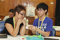 New York, NY, USA - June 23, 2012: Phoebe and Jaison Yee, from Smithtown, NY, learn to fold a modular Origami model called Bascetta Star in a class taught by Sang Yul Bae. The students are some of the many attendees at the annual OrigamiUSA 2012 convention held at Fashion Institute of Technology in New York City. Experts teach classes of students how to fold various Origami designs from simple to highly complex.
