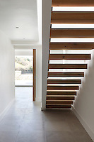 A cantilevered contemporary staircase filters light from an upstairs window into the hallway below