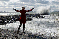 Woman standing on Merivälja pier in Tallinn. Storm waves.