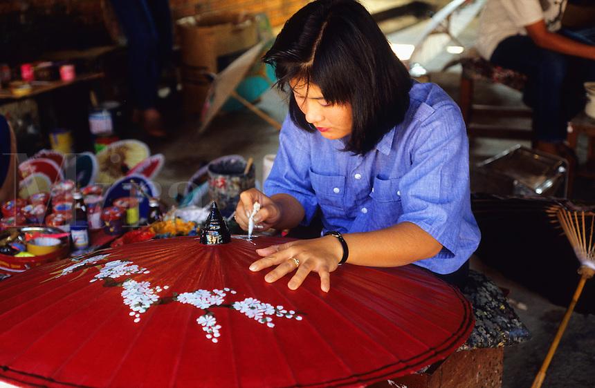 Thailand. Chieng Mai.  Girl artist hand painting designs onto paper umbrella.