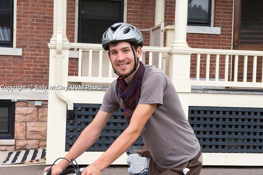 UVM Student Jens Pharr rides a bicycle to collect compost on campus.  Revolution Compost.