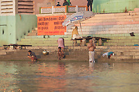 Devotees performing morning Puja in Ganges river Jain Ghat, Varanasi, India