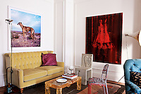 A yellow velvet Arts and Crafts sofa and contemporary artwork in one corner of the living room