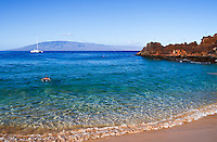 A snorkeler explores the reef at Ka'anapali Beach, Maui; more snorkelers explore the area around Black Rock, which is the northern point of the beach in the distance.