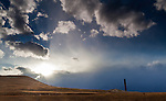 The iconic Anaconda Smelter Stack is seen near sunset with bright light rays bursting through the clouds, illuminating the surrounding landscape.
