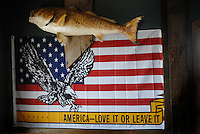 The interior of the private fishing marina in Pointe Aux Chene, Louisiana, with a sign reading 'America - love it or leave it' below a plastic fish.
