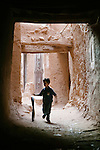 A boy roles a bicycle tire down a narrow walkway, Morocco