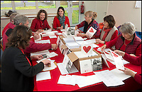 BNPS.co.uk (01202 558833)<br /> Pic: TomWren/BNPS<br /> <br /> 'Cupids' hard at work making sure all the online orders are written and sent.<br /> <br /> A British village is cashing in on the cupid effect this Valentine's Day by launching its own postal service so anyone can send a card from the 'world's most romantic village'.<br /> <br /> The tiny village of Lover in Wiltshire has launched the 'Lover Post' with limited edition cards and a special post mark showing it has been sent from the tender-hearted village.<br /> <br /> The quirky gimmick is part of a campaign to save the once-thriving village for the local community.