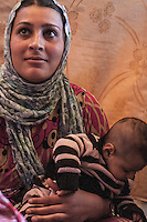 June 11, 2015 - Bekaa Valley, Lebanon: Mariam Edriz, a Syrian refugee woman holds her baby inside a tent in a temporary shelter settled in Saadnayel city in east of Lebanon. Her baby was born stateless after she fled from Idlib her hometown, when opposition armed groups started battling against the government of President Bashar Al-Assad. (Photo/Narciso Contreras)