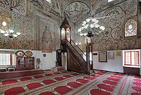 Minbar or pulpit, mihrab, prayer carpets and frescoes in the Et'hem Bey Mosque or Xhamia e Et'hem Beut, begun 1789 by Molla Bey and finished in 1823 by his son Haxhi Ethem Bey, great-grandson of Sulejman Pasha, Tirana, Albania. The frescoes decorating the mosque, unusual in Islamic art, depict swirling vegetal patterns. The mosque is listed as a Cultural Monument of Albania. Tirana was founded by the Ottomans in 1614 by Sulejman Bargjini and became the capital of Albania in 1920. Picture by Manuel Cohen