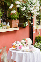 A multi coloured selection of freshly cut roses on a garden table covered with a crispy white tablecloth
