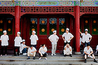 Members of the catering staff take a short break in the fresh air in The West Lake Restaurant's front square. Able to seat up to 5,000 people at one sitting, The West Lake Restaurant is the biggest Chinese restaurant in the world. Each week its diners, who staff are taught are 'the bringers of good fortune', devour 700 chickens, 200 snakes, 1,200 kgs of pork and 1,000 kgs of chillis. Its 300 chefs cook in five kitchens and its staff total more than 1,000.It is fully booked most nights.