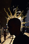 """Young street kid with spiked mohawk along """"The Ave"""" University District, backlit silhouetted, Seattle, Washington State USA"""