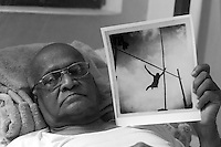 Fr. Lucian Dep holding a photograph of himself - pole vault at St. Joseph's College, 1949