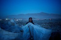 An Afghan Pashtun boy scavenges for recyclables at a garbage dump site in Kabul.