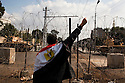An Egyptian anti-government protester raises a fist as he chants slogans against President Hosni Mubarak outside the heavily guarded Orouba Presidential Palace February 11, 2011 in the Heliopolis district of Cairo, Egypt. Protesters marched Friday on a number of public buildings including the palace in an effort to spread their ongoing protests that are now in their 18th day. .(Photo by Scott Nelson)