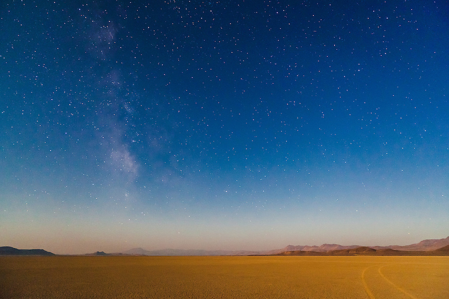 The stars and Milky Way galaxy are seen above curving tracks in the desert playa in the Alvord Desert, Southeast Oregon.
