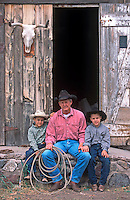 Cowboy and grandsons pose in front of old barn.