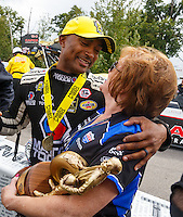 Aug 20, 2016; Brainerd, MN, USA; NHRA top fuel driver Antron Brown (left) is congratulated by sponsor Charlotte Lucas as he celebrates after winning the Protect the Harvest Nationals from Seattle, WA that was delayed by rain to run during qualifying for the Lucas Oil Nationals at Brainerd International Raceway. Mandatory Credit: Mark J. Rebilas-USA TODAY Sports