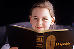 Young girl in prayer reading the bible smiling Bothell Washington State USA  MR