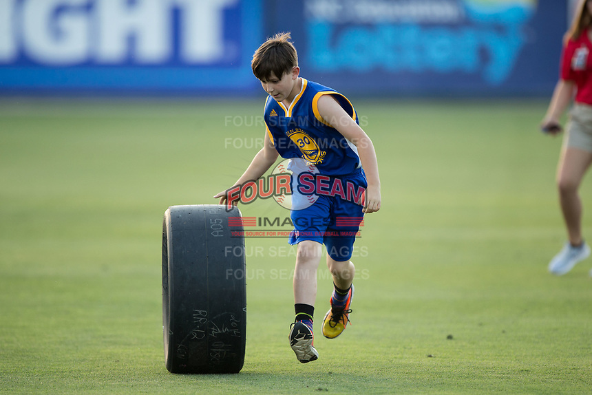 A young fan competes in a tire race between innings of the South Atlantic League game between the Hickory Crawdads and the Kannapolis Intimidators at Kannapolis Intimidators Stadium on May 18, 2017 in Kannapolis, North Carolina.  The Crawdads defeated the Intimidators 6-4.  (Brian Westerholt/Four Seam Images)