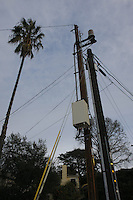 A cell phone antenna (cylinder, right of upper center) and large control box are mounted on a sepearte utility pole behind an existing one near the Intersection of Catalina Boulevard and Naragansett in Ocean Beach, January 3, 2008.  At least one neighbor near the site was unaware of what the antenna was.