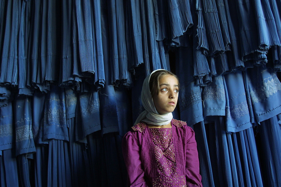 A girl waits for her mother to buy a new burkha in a shop in Kabul. Most women in Afghanistan wear burkhas in stead of scarves or other veils, to avoid being harassed on the streets.