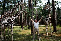 Howard Gilman at White Oak Plantation with his giraffes. White Oak is a 75,000 acre wildlife breeding, research and training facility in Nassau County. <br />