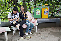 Vietnam. Hanoi. A couple of lovers at Noan Kiem lake. Romantic moment. The young man plays with his mobile phone. Two public bins, one green, the other yellow, for recycling waste. 04.04.09 © 2009 Didier Ruef