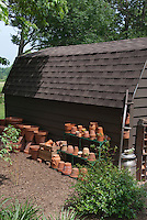 Garden shed potting shed with stacks of terra cotta pottery pots containers ready to use for planting