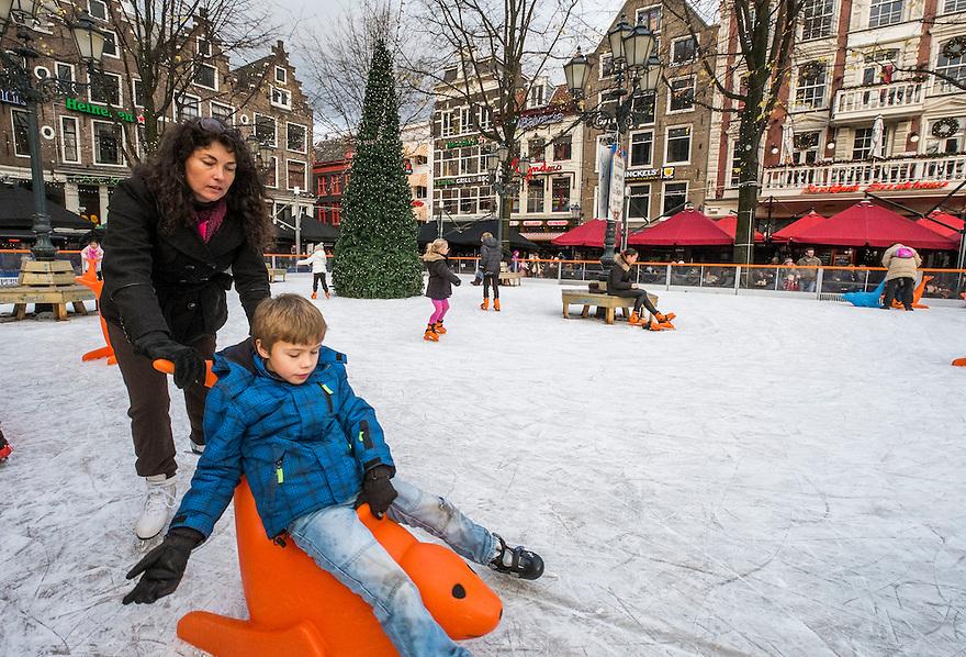 Nederland, Amsterdam, 13 dec 2014<br /> In de winter rond kerst is er op het Leidseplein een kleine schaatsbaan. Veel kinderen van toeristen kunnen er op gehuurde schaatsen zich even vermaken terwijl ouders helpen met het leren schaatsen zo ver dat nodig is. <br /> Foto: (c) Michiel Wijnbergh