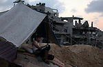 A palestinian man sits under a tent among a destroyed house after returning home in the Tufah neighbourhood in eastern Gaza City on August 31, 2014. Calm returned to the coastal enclave in a August 26 ceasefire, and Gazans were gradually starting to rebuild their lives after a bloody and destructive 50-day war, the deadliest for years. Photo by Ashraf Amra
