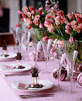 Miniature lanterns are used as place setting whilst large bunches of pale pink tulips and roses are used as centerpieces