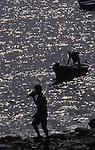 Silhouette of man holding fish with boat in the background.Los Abrigos, Tenerife, Canary Islands.
