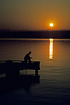 Sunrise with older man silhouetted fishing off dock on lake Washington with Cascade Mountains Seattle Washington State USA.