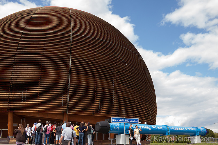 "A tour group going into the domed hall containing the ""Universe of Particles"" exhibit on Square Galileo Galilei at CERN, (Conseil Européen pour la Recherche Nucléaire), the European Organization for Nuclear Research, Geneva, Switzerland"